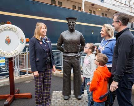 Next to the statue of Britannia's longest serving Royal Yachtsman, Ellis 'Norrie' Norrell MVO RVM, Diane, Visitor Assistant, chats to visitors.