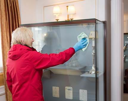 Linda, Housekeeping Team Leader, polishes a glass cabinet in the State Dining Room.