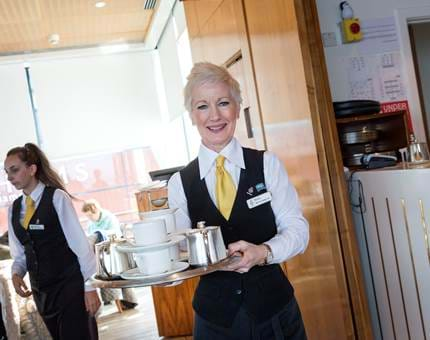 Rosie, Waiter, serves visitors hot beverages in the Royal Deck Tea Room.