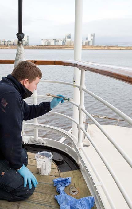 Painting stanchion rails on the aft section of the Royal Deck.