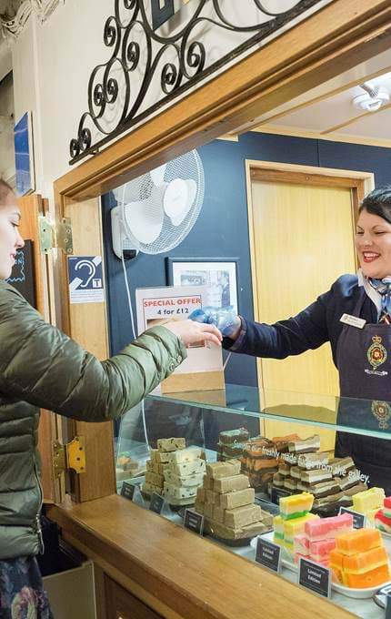 Sales assistant offers fudge samples in the NAAFI.