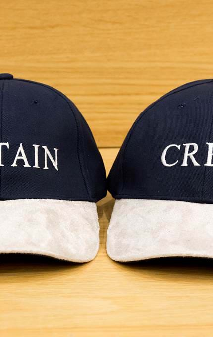 'Captain' and 'Crew' caps.