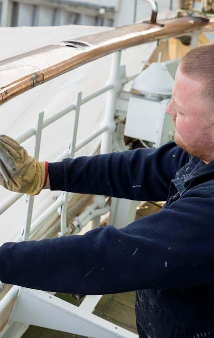 Sanding the handrail stanchions on the Royal Deck aft.
