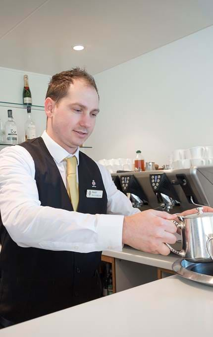 Waiter prepares hot beverages to be served.