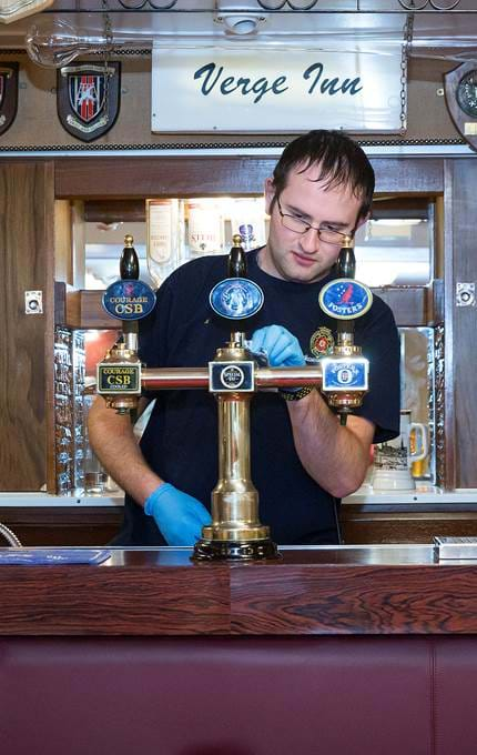 Janitor polishes the taps at the bar in the Petty Officers' Mess.