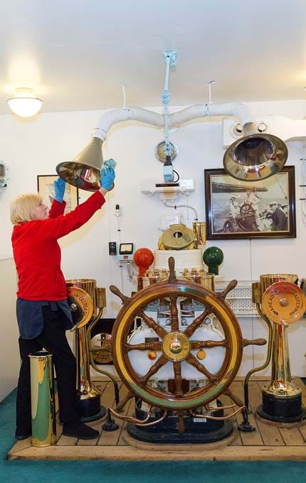 Housekeeper polishes the voice pipes on the original wheelhouse.
