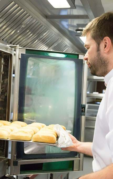 Chef removes bread rolls.