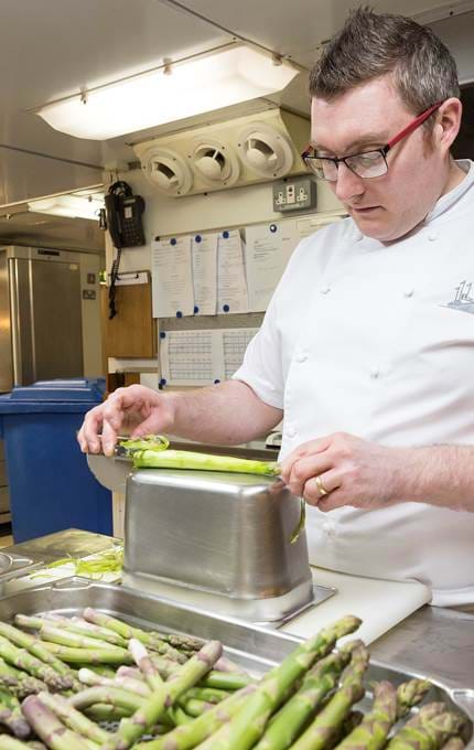 Chef prepares asparagus for evening meal.