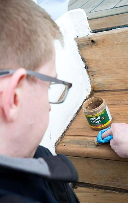 Applying wood filler to the screw head.