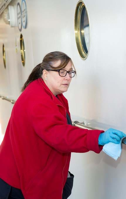 Housekeeper polishes handrail.