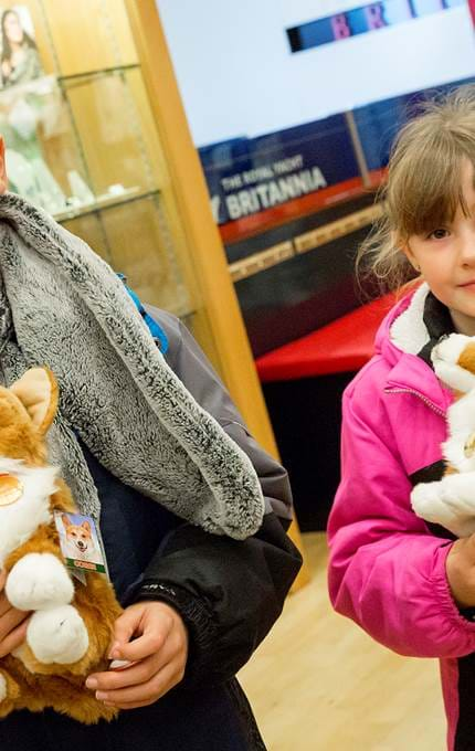 Young visitors with corgie toys.