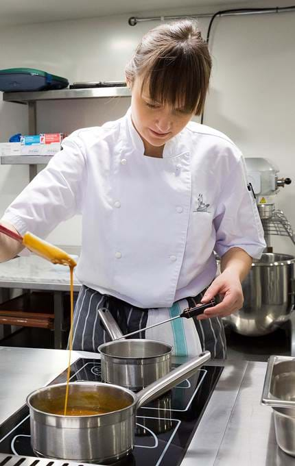 Commis chef makes caramel sauce.