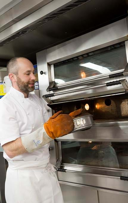 Chef removes freshly baked cakes from oven