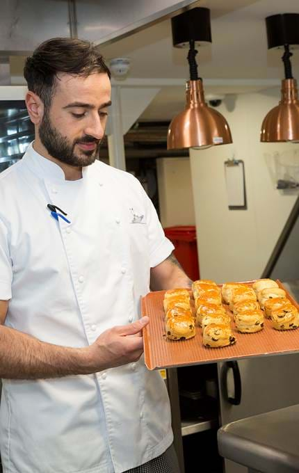 Chef holds plate of scones in kitchen