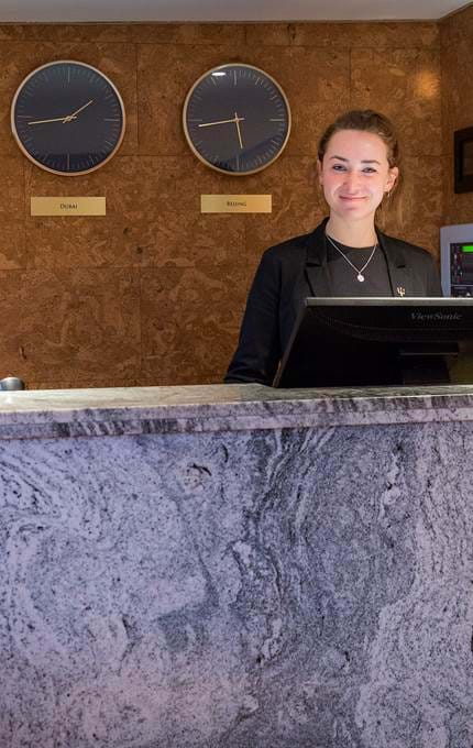 Guest Services Assistant is ready at reception to welcome guests aboard Fingal.